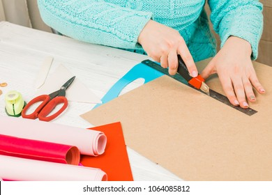 Handmade, the girl cuts out of paper. scrapbooking for a wedding or other holiday decorations. Tools for scrapbooking.