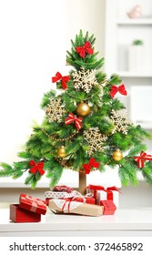 A handmade green Christmas tree and presents on the table, in the room