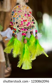 Handmade green and violet bijouterie with gems, tassels and feathers,america selective focus. Tourist market in Brazil