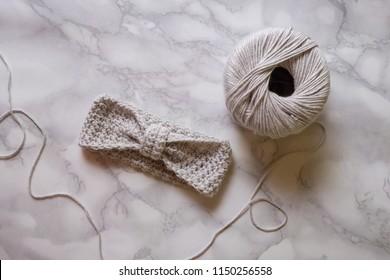 Handmade grey crochet headband, made of crocheting cotton yarn, marble luxury background