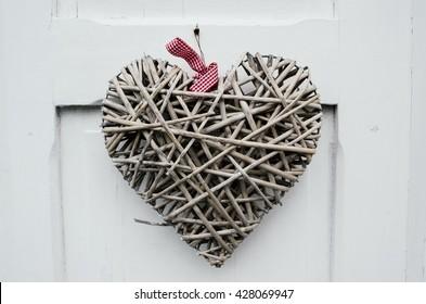 Handmade heart from branches hanging on white door in Stavanger closeup