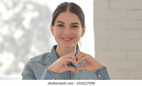 Handmade Heart Gesture by Smiling Young Girl