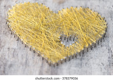 Handmade heart made of nails on wooden board with wowen gold string