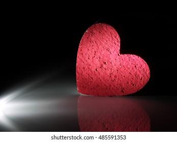 handmade heart painted with red gouache under spot light
