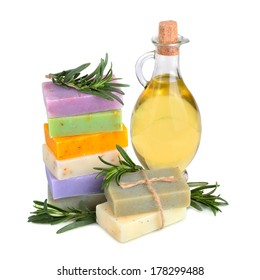 Handmade herbal soaps with rosemary twigs and massage oil on white background