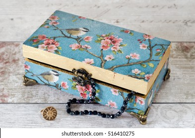 A handmade jewellery box decoupaged with vintage papers and gilded with gold leaf