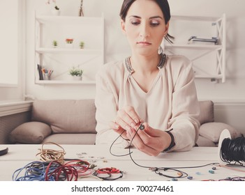 Handmade jewelry making, female hobby. Young woman creating bracelets at home workshop. Fashion, handicraft concept