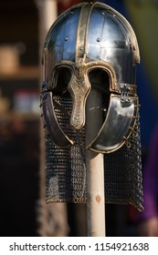 handmade knight's helmet presented on a wooden stick in front of dark background