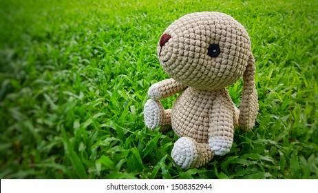 Handmade knitted doll. Bunny toy. Crochet stuffed animals. Miniature crochet rabbit. Brown bunny on green grass background.