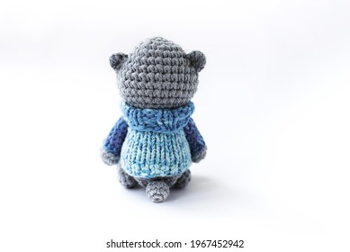 Handmade knitted soft toy. Amigurumi. Small  teddy bear  in the blue sweater on the white background. Crochet stuffed animals. Sits with his back