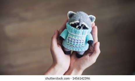 Handmade knitted toy. Amigurumi racoon toy. Crochet stuffed animals.