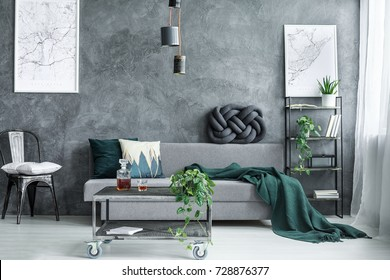 Handmade knot cushion lying on a grey sofa in modern living room with plants