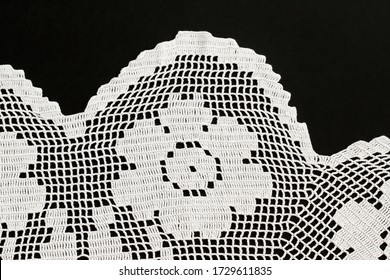 Handmade lace white color tablecloth with rose motif on black surface.Top view