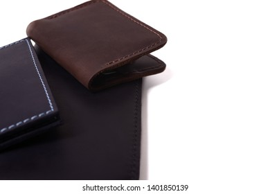 Handmade leather brown cardholder, blue passport cover and black purse isolated on white background closeup. Stock photo of isolated handmade luxury accessories.