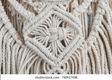 Handmade macrame braiding, background thread on a wooden Board top view