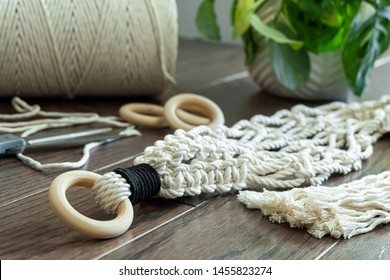 A Hand-Made Macrame Plant Hanger with Wooden Rings on a Beautiful Wooden Background Setting the Mood for Creativity. This Macrame has a black highlight wrapped near the top.