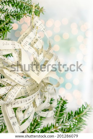 Handmade music sheet ornament hung from a Christmas tree with lights in the background. Shot with copy space.