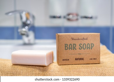Handmade natural bar soap in recycled paper packaging with a sink in the background. Concept of using plastic free shower products to save our planet