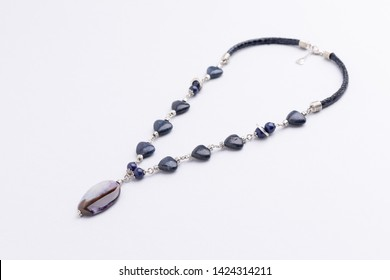 Handmade necklace with lapis lazuli and ahat stone beads, studio photography. Handmade jewelry background with copy space, close up necklace with semi precious stones. Gemstone long necklace.