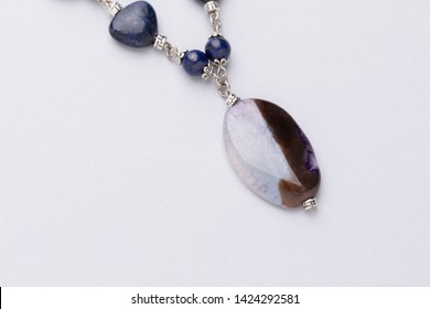 Handmade necklace with semiprecious stone pendant and beads. Jewelry detail extreme close up with copy space. Lapis lazuli and ahat stone jewellery.