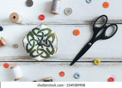 Handmade and needlework. Handmade pin cushion with a simple ornament and a pair of black scissors on a white table. Buttons and threads in the background. Top view