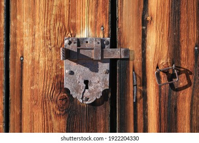 Handmade old lock on a weathered wooden door.