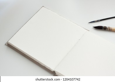 Handmade old-fashioned watercolor sketchbook with two artistic brushes, opened on a blank page. Photo can be used as a mockup for displaying of sketches and paintings.