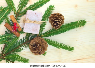 Handmade organic Soap with Cinnamon, Pine and Pinecones top view on wood board