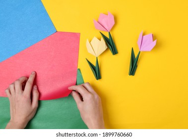 Handmade origami from colored paper. Woman making origami tulips on a colored background