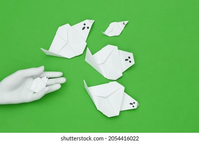 Handmade origami ghosts and mannequin hand on green background. Halloween theme. Top view