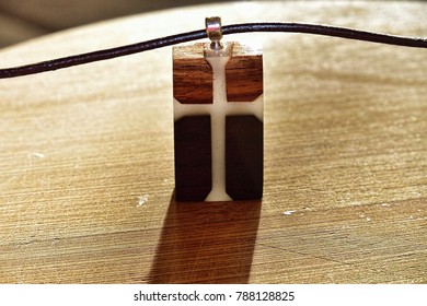 Handmade ovangkol and sandal hardwood pendant with latin cross pattern and glowing epoxy