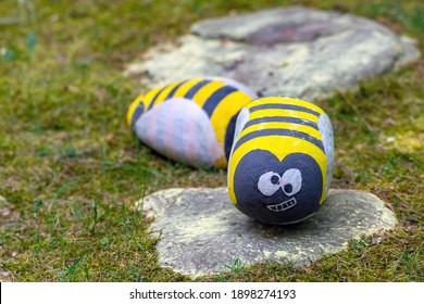 Abeille en pierre acrylique peinte à la main dans le jardin.