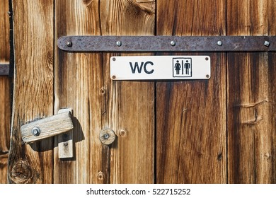 Handmade painted toilet wc sign on wooden door of farmhouse