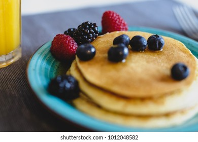 Handmade pancakes with fresh wild berries and maple syrup. Selective focus on the berries