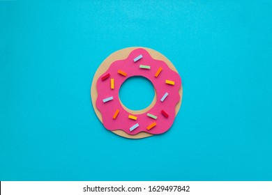 Handmade paper art strawberry donuts with colorful sprincles on blue paper background. Paper cutting, 3d illustration.