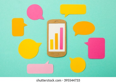 Handmade paper model of smart phone with growth chart and speech bubbles - useful image for mobile marketing, mobile commerce or advertising