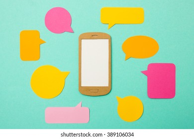 Handmade paper model of smartphone with blank screen and many speech bubbles - useful image for mobile marketing, customer support, advertising for cell phone plans or chat flatrate