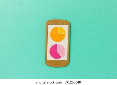 Handmade paper model of smartphone with pie charts - image concept for analytical apps, accounting, financial reporting, customer research