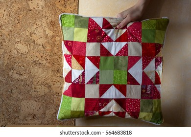 Handmade patchwork cushion with Christmas star pattern in Christmas colors green and red behind the cork wall in the woman's hand