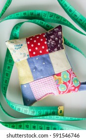 handmade pin cushion in style patchwork and sewing centimeter lying on a white background, top view.