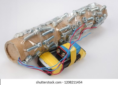 Handmade pipe bomb with cell phone firing device on white background