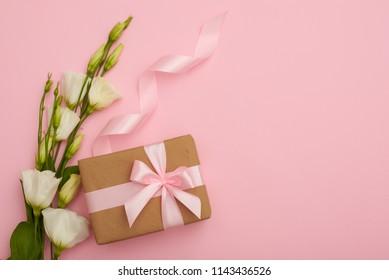 Handmade present box with eustoma flowers on pink flatlay