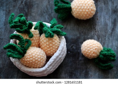 Handmade product from knit  on grey wooden background, group of pineapples fruit in yellow with green leaf from amigurumi art for interior design