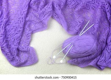 Handmade purple scarf and knitting set on white wool background