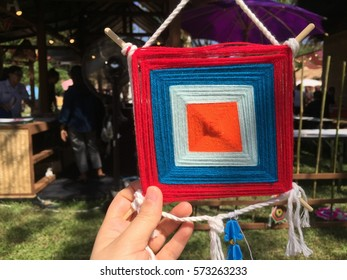 Handmade red, blue, white and orange crochet frame pattern, knitting, sewing. Homemade colorful mobile.