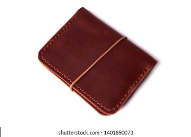 Handmade red color leather cardholder with rubber band isolated on white background closeup. Stock photo of handmade luxury accessories.