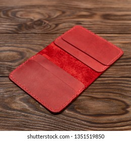 Handmade red leather cardholder on wooden background. Cardholder have 4 pockets for cards. Stock photo with soft focus background.