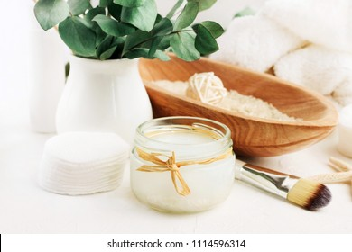 Handmade rice water for domestic holistic skin cleansing in glass jar, wooden bowl of rice, white table & towels, aroma green leaves decor.