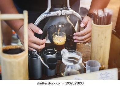 Handmade Rok coffee maker espresso shot with outdoor lighting.