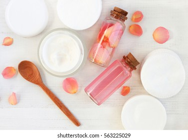 Handmade rose extract cosmetic. Tonic and cream, cotton pads, bottles, fresh pink flower petals, wooden table preparation background.